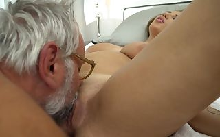 A busty blonde is getting some old dude's cum on her boobs